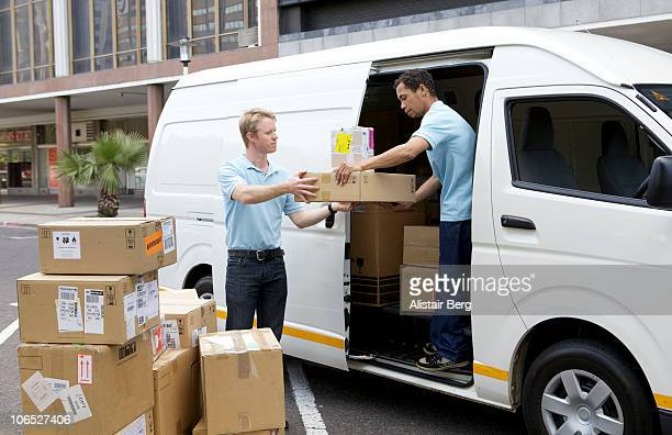 Two couriers loading a van with boxes