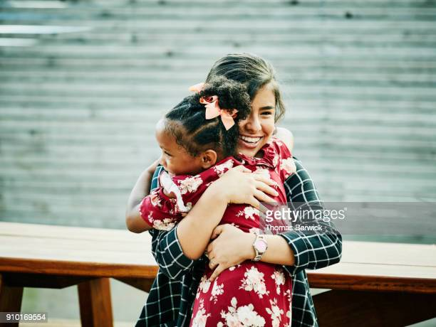 two cousins hugging before outdoor family dinner party - community support stock pictures, royalty-free photos & images