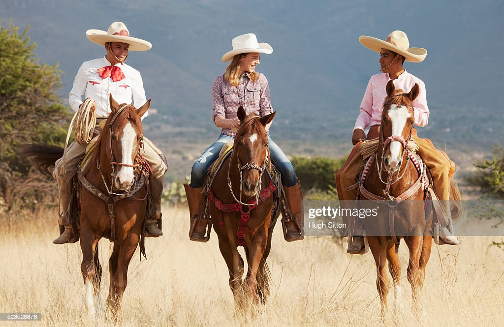 Two cowboys and woman riding horses : Stock Photo