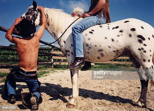 Two Cowboys one on a spotted horse and the other bare chested adjusting the reigns USA 2004
