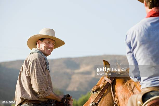 Two cowboys riding horses