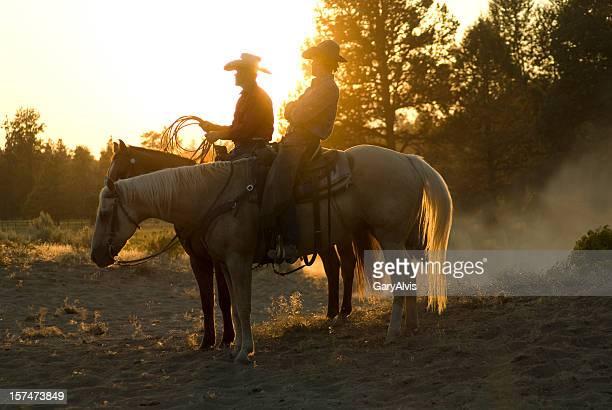 Dos de los cowboys sentado en los caballos en puesta de sol
