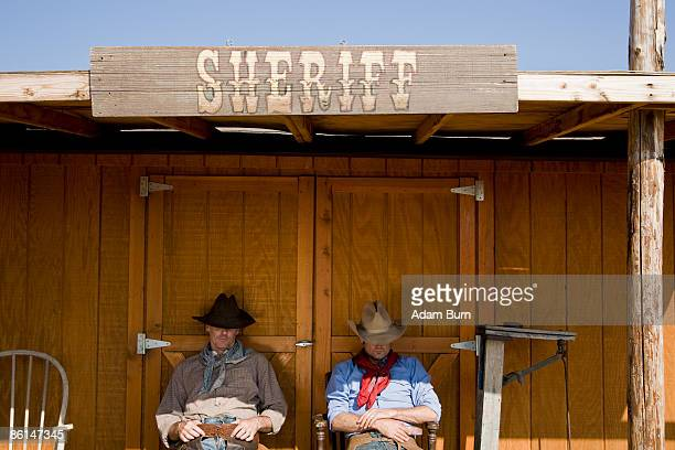 Two cowboys sitting outside the office of the Sheriff