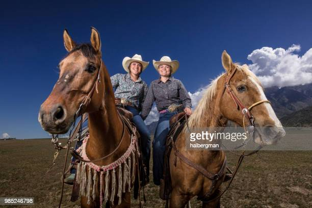 Two Cowgirls on Horseback Leaning Close