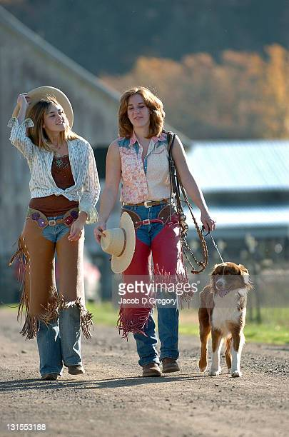 Two cowgirls walking down road, autumn