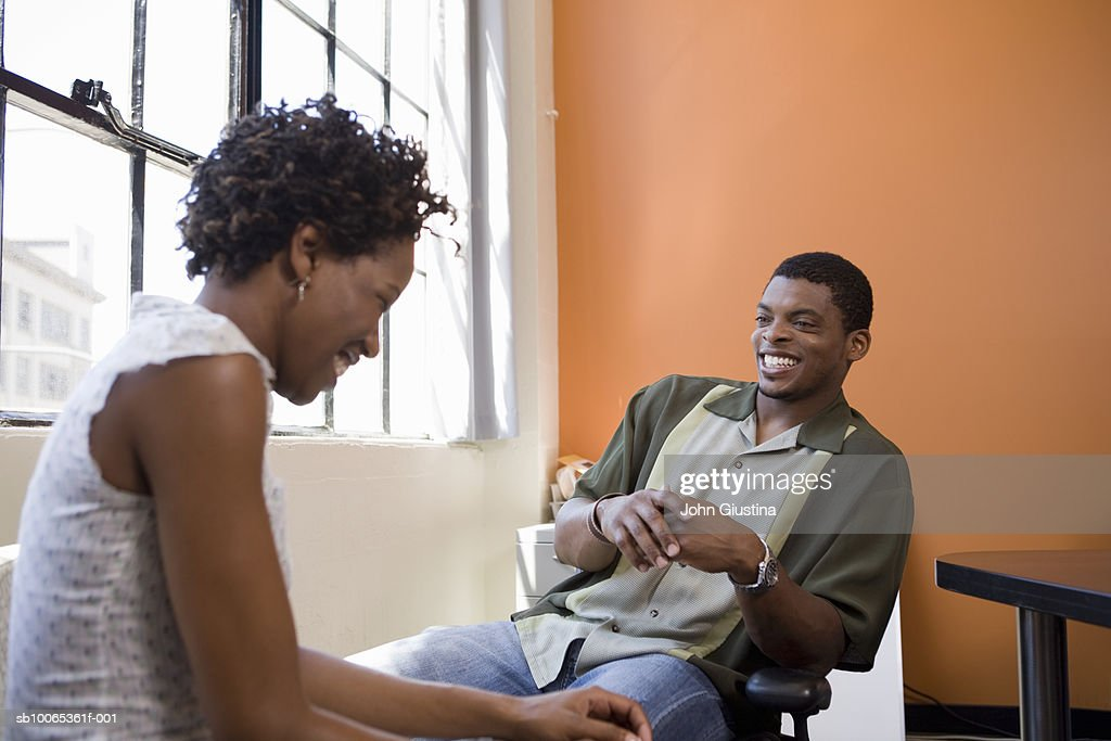 Two co-workers chatting and laughing in office : Foto stock