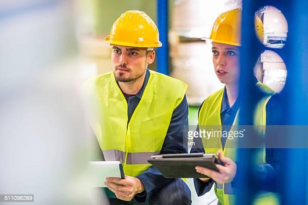 Zwei Kollegen, die Artikel in the Warehouse