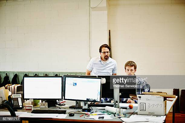 Two coworkers discussing project on computer
