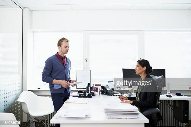 Two coworkers in discussion in an office