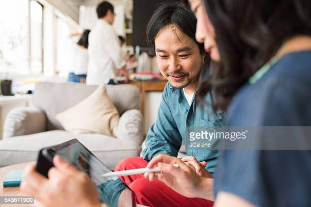 Two coworkers looking at a digital tablet
