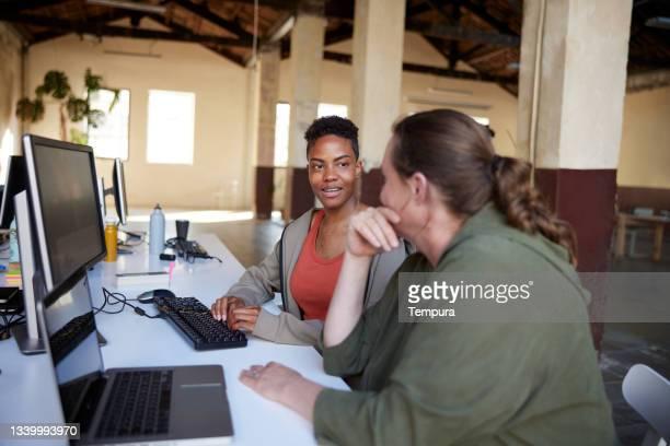 dos compañeros de trabajo hablando y sentados frente a sus computadoras. - compromiso de los empleados fotografías e imágenes de stock