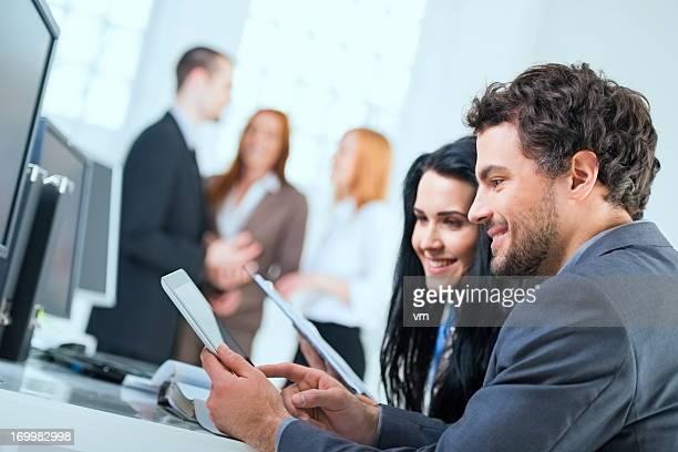 Two coworkers working on digital tablet