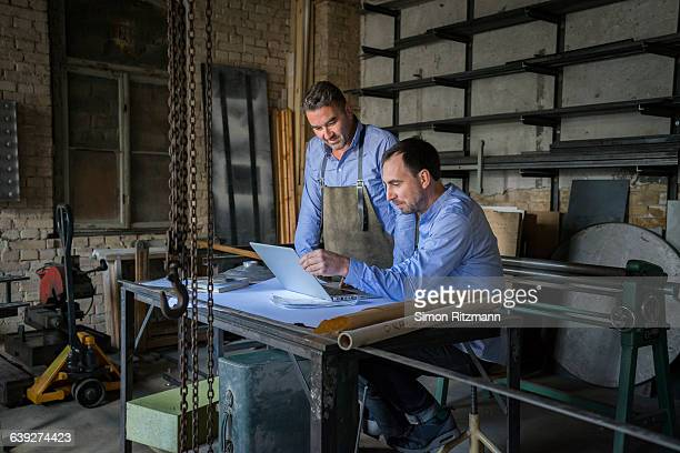 Two craftsman using laptop in workshop