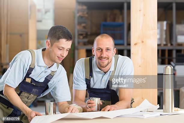 Two craftsmen with metal mugs talking