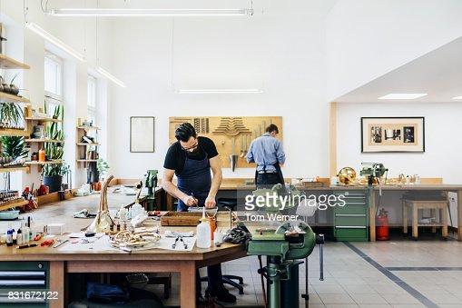Two Craftsmen Working Together In Musical Instrument Workshop