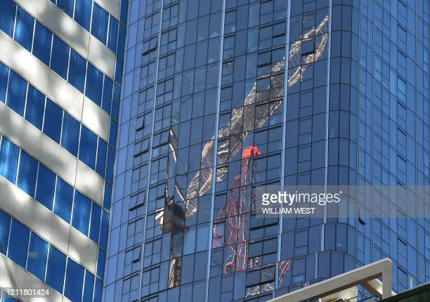 Two cranes are reflected on the side of a highrise building in Melbourne on May 5 2020 Australia's economy is losing 4 billion Australian dollars...