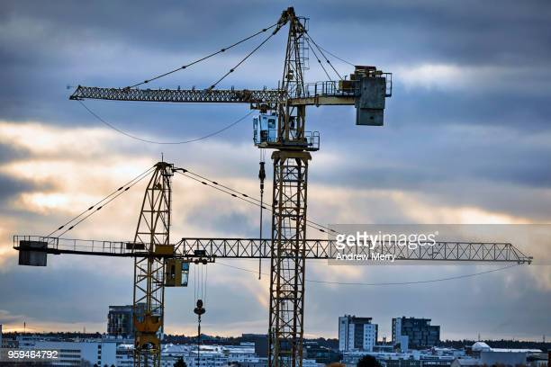 two cranes with dramatic afternoon sky, oulu, finland - urban renewal stock pictures, royalty-free photos & images