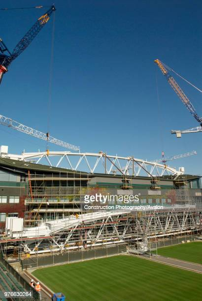 Two cranes work in tandem to lift roof trusses on to fixed roof of Centre Court, All England Lawn Tennis Club, Wimbledon, London, UK, 2008.