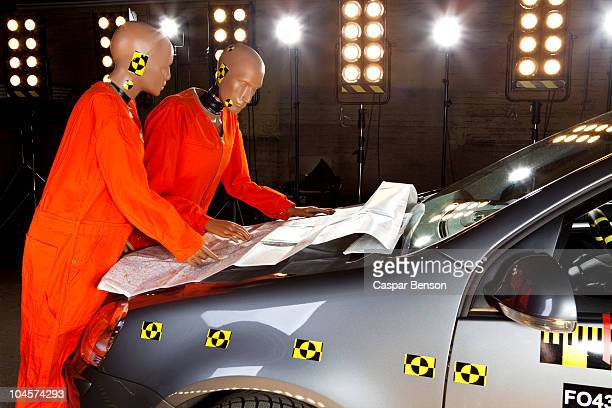 Two crash test dummies looking at a road map