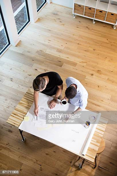 Two creative businessmen discuss project in office