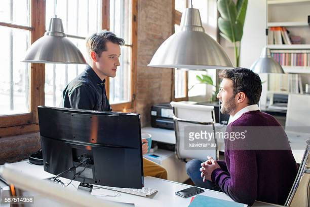 Two creative businessmen talking in the office