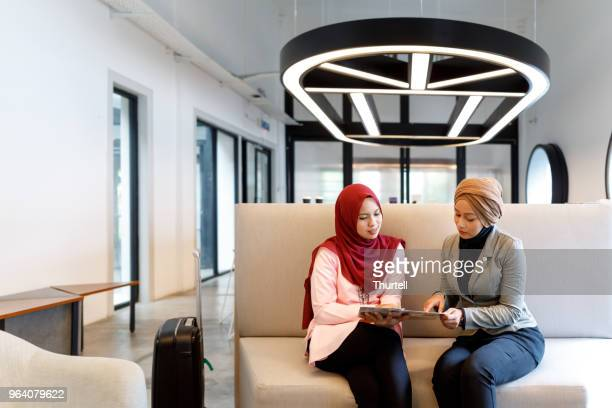 two creative muslim women discussing ideas - malay hijab stock photos and pictures