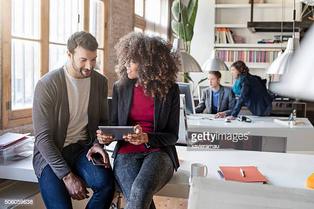 Two creatives checking a project in the digital tablet