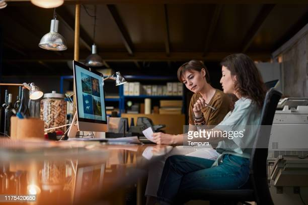 two creatives sharing a computer and doing paper work. - small office stock pictures, royalty-free photos & images