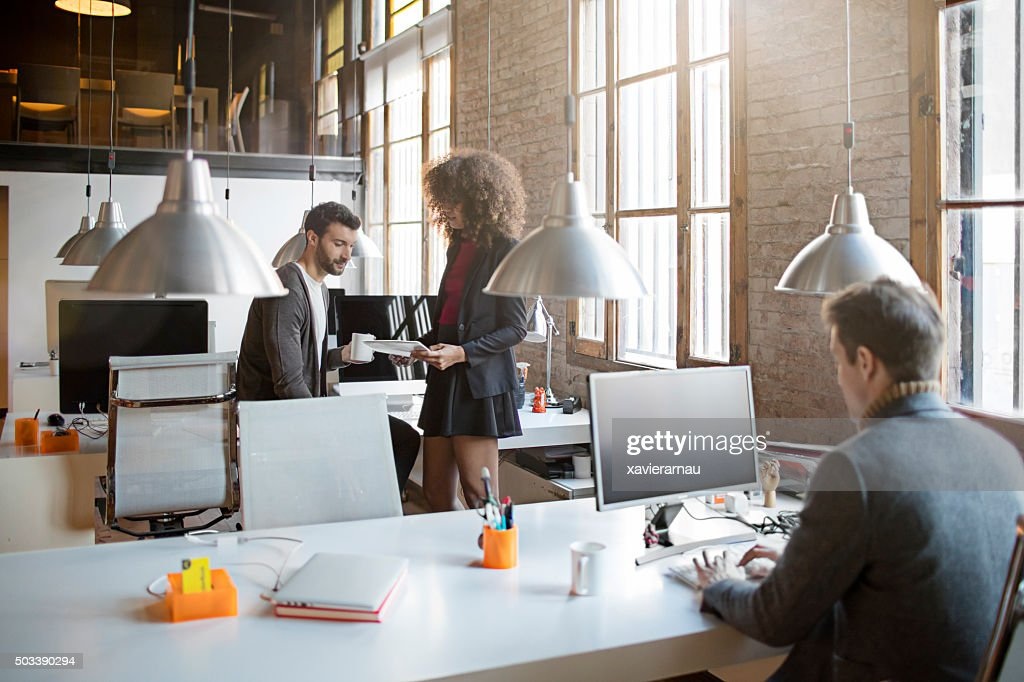 Two creatives talking in the office : Stock Photo