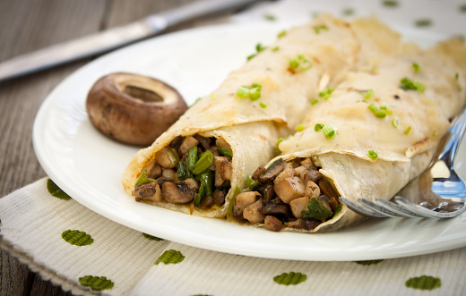 Two crepes filled with savory herbs and mushrooms 175384343