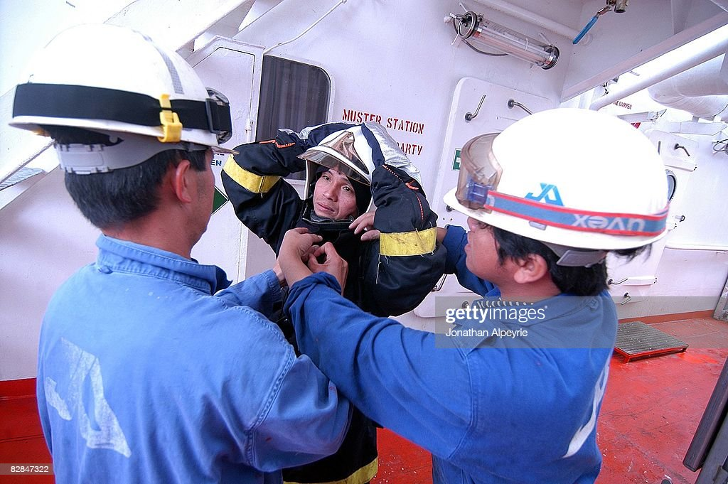 Two crew members are helping another to put on the heavy anti fire clothing, on July 16, 2008, in France. A group of specialized crew members trained in fire fighting are on each tanker of the company.