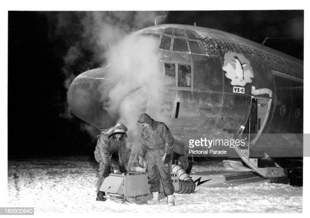 Two crew members of the 'Hercules', that mad the first historic flight to the Antarctic during the winter, are seen preheating the aircraft at Naval...
