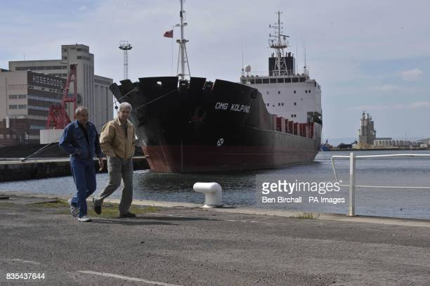 Two crew members walk around the OMG Kolpino Russian cargo ship pictured at Avonmouth docks Bristol where its crew of 12 sailors have been marooned...