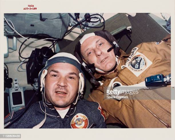 Two crewmen of the joint USUSSR ApolloSoyuz Test Project pictured during a visit by the US astronauts to the Soviet spacecraft on 17th July 1975 They...