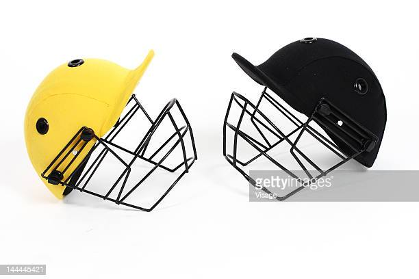 Two cricket helmets facing each other , studio shot