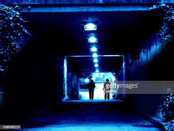 two criminals waiting for their victim in a dark tunnel - gruesome crime scene photos stock pictures, royalty-free photos & images