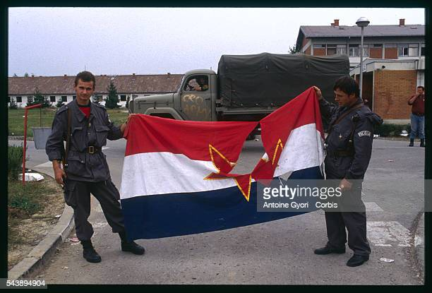 Two Croatian soldiers hold a Yugoslavian flag bearing a hole in the center after fights against the Yugoslavian army and the Serbian militias during...