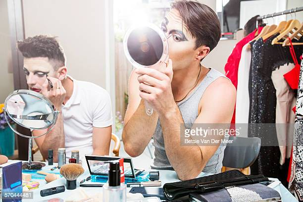 Two cross dressers applying make up at home.