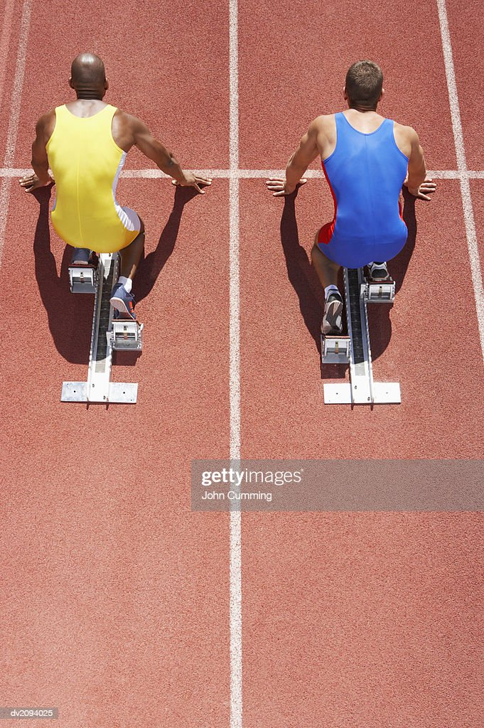 Two Crouching Athletes Lined Up on Starting Blocks on a Running Track : Stock Photo