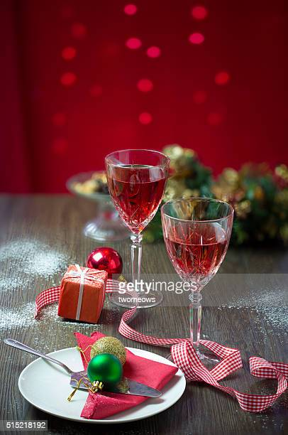 Two crystal wine glasses with red wine on Christmas party table top.