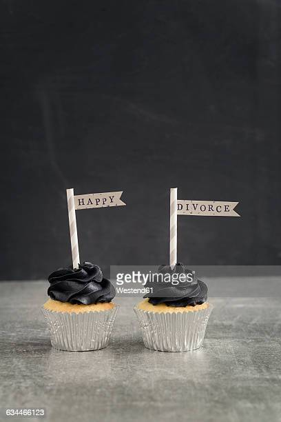 Two cup cakes with black coloured buttercream topping and pennons