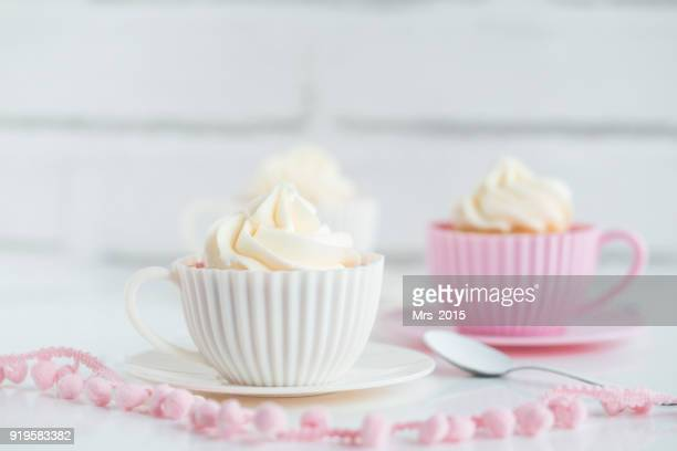 Two Cupcakes with buttercream frosting in teacups