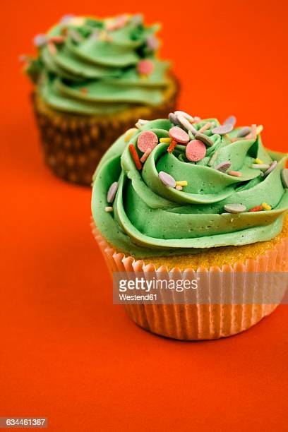 Two cupcakes with green cream and baking dekor in front of red background
