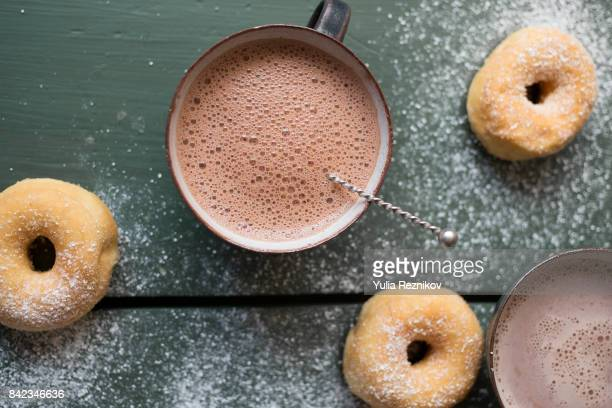 Two cups cappuccino with donuts