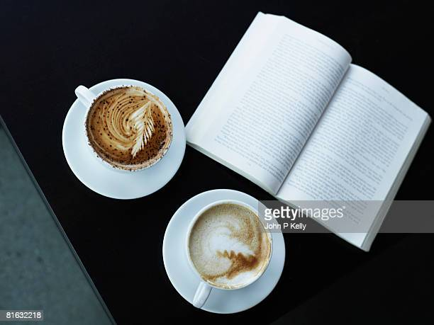 Two cups of cappuccino, and a book, sitting on table.