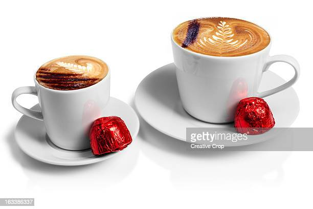 Two cups of cappuccino coffee with chocolates