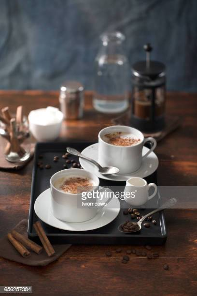 Two cups of cappuccino on wooden table top.