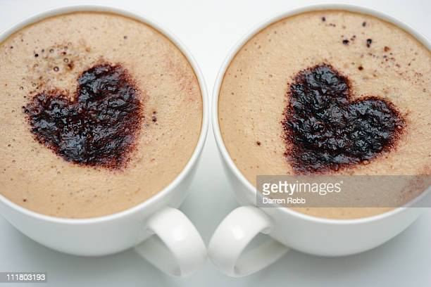 Two cups of cappuccino with love heart decoration