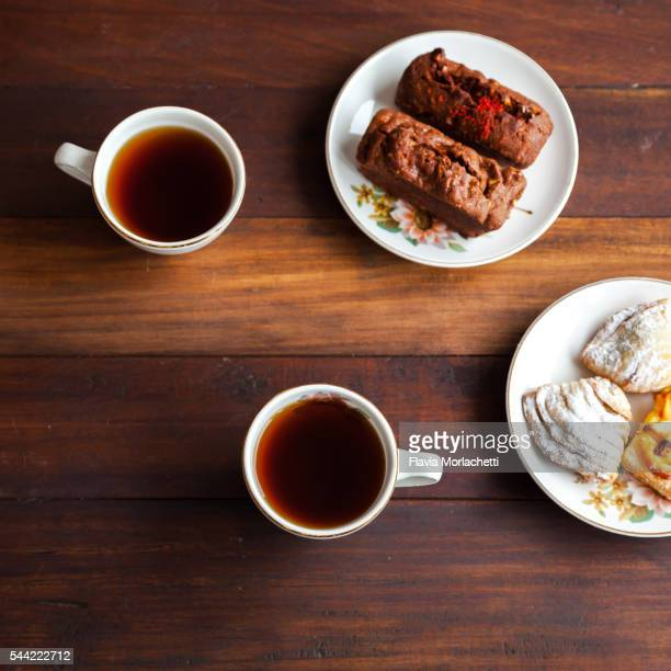 Two cups of coffee and pastries over table