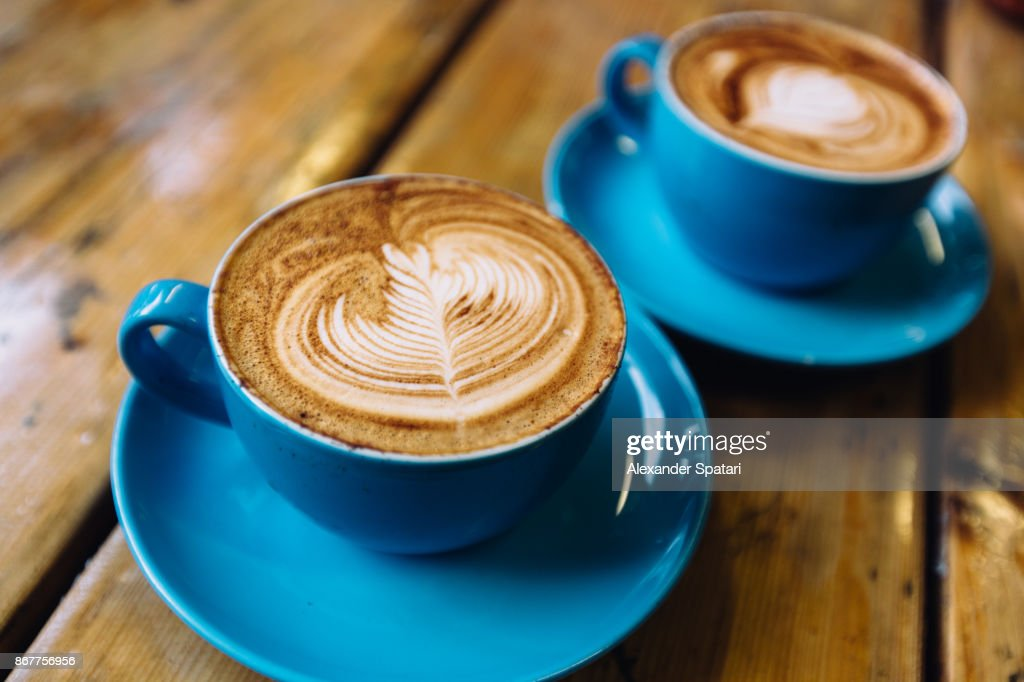 Two cups of coffee in blue cups on a wooden table close up : Stock Photo